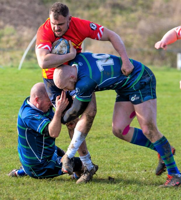 Isle of Wight County Press: Ventnor's Harry Colson tries to wrestle his way through Overton's defence.