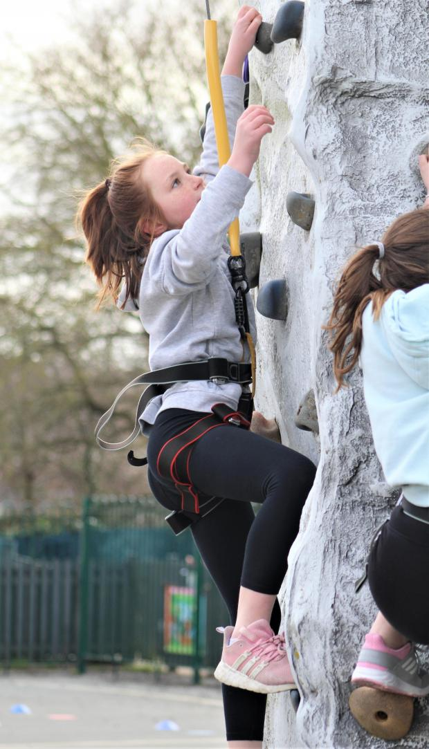 Isle of Wight County Press: Summer Trevillion, aged ten, focuses on the next step of the climbing wall.