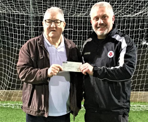 Isle of Wight County Press: Caulkhead Strollers founder, Dave Duffy, left, presents a cheque for £3,000 to Brading Youth chairman, Mark Powell, who will take disability youth and junior players from the disbanded Strollers.