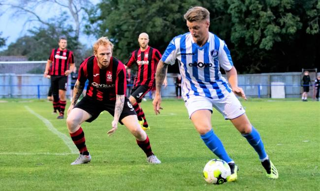 Cowes forward Jimmy Wykes (in blue) in action in last night's FA Cup tie against Totton and Eling at Westwood Park.  Photos: Barbara Close