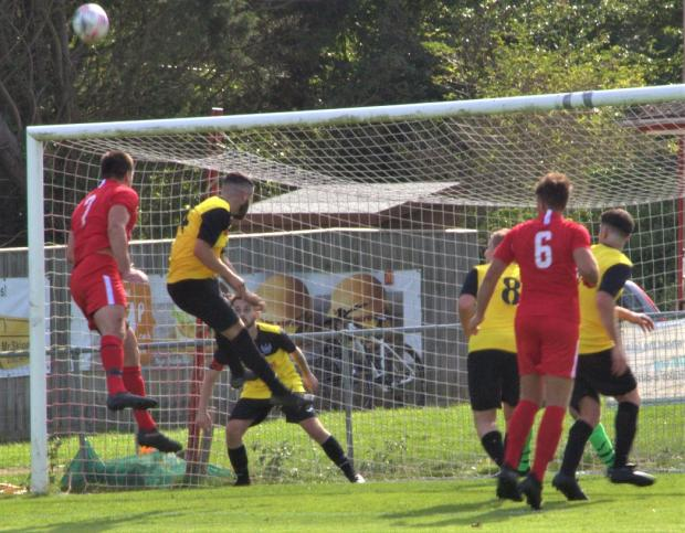 Isle of Wight County Press: Sandown (in yellow) clearing their lines against Brading Town in Division 1's 'Bay' derby.