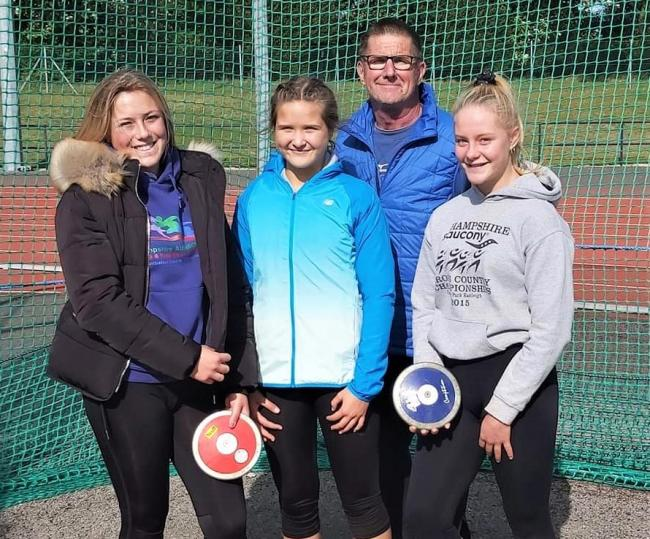 From left, Ellie Lovett, Naomi Holdsworth and Evie Taylor with discus coach Mike Ferne.