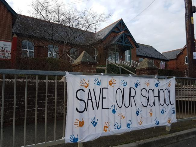 A 'Save Our School' banner hung outside Chillerton and Rookley Primary School by parents.