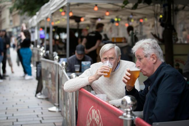 Members of the public enjoy their first drink in a beer garden in Scotland