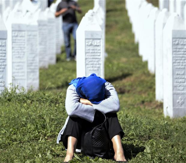 Isle of Wight County Press: A grieving Muslim at one of the many Bosnian war graves.