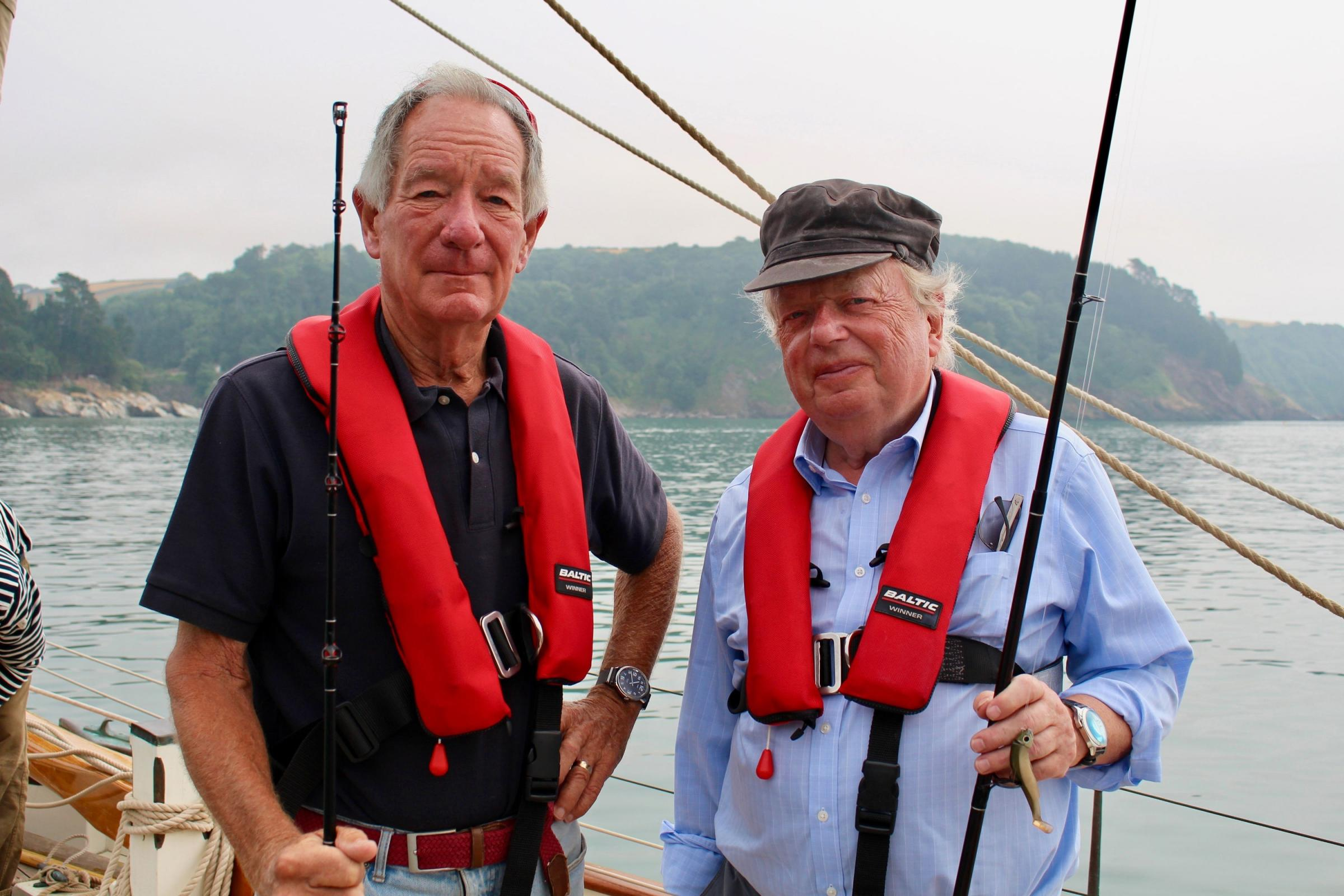 John Sergeant and Michael Buerk holding fishing rods on Bonaventure (yacht) at sea.