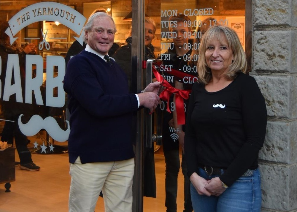 Carnival Committee Chairman Chris Waddington cuts the ribbon with Yarmouth Barber owner Tanya Letchford. Picture by Saffie Letchford.