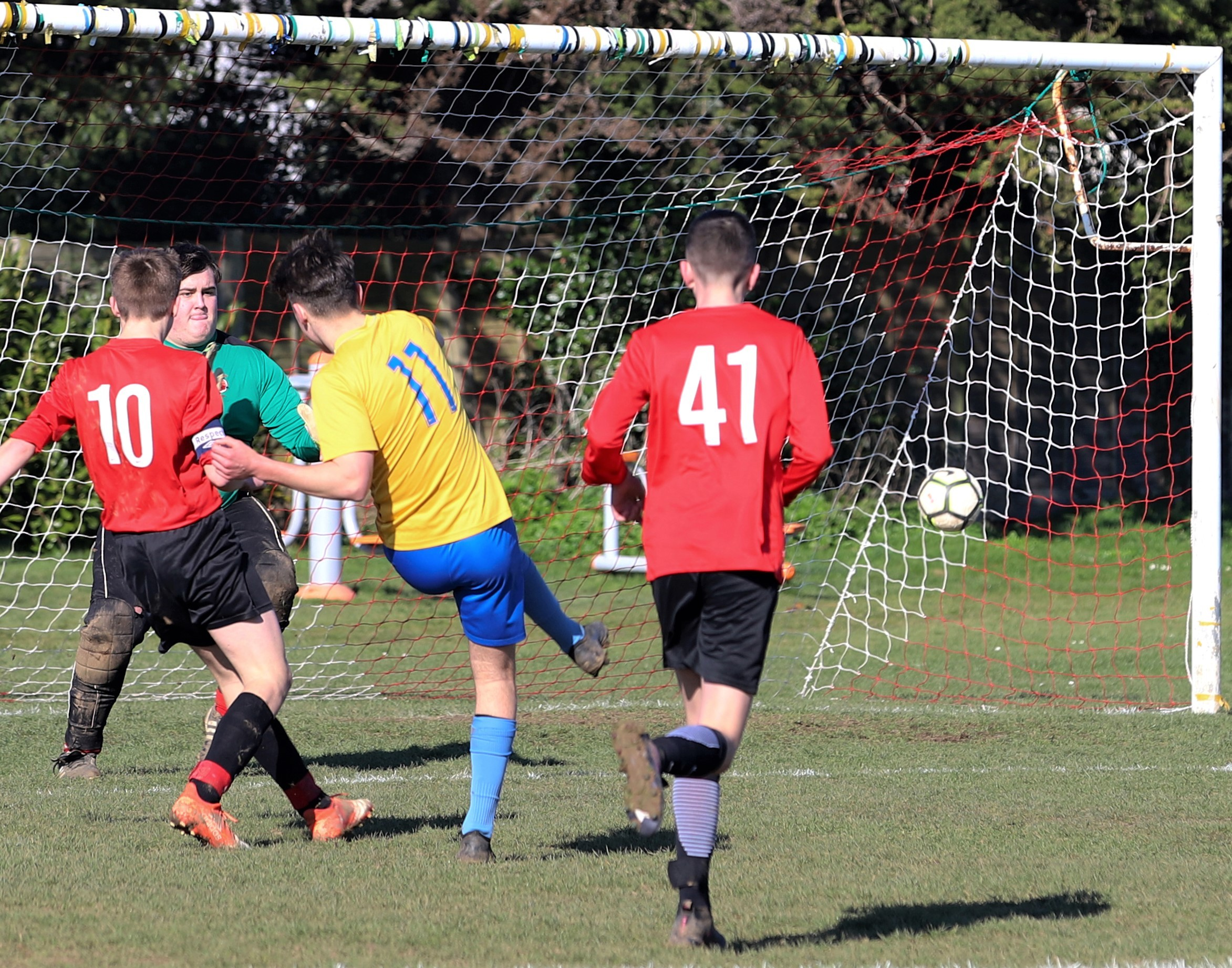 Newport's Ben Snow (in yellow) fires home against Brading in the IW U16 Cup semi-final at Steyne Park, Bembridge.  Photos: Paul Blackley