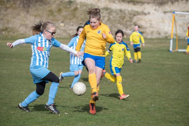 Isle of Wight County Press: Francesca Peck, left, of Vectis Youth U9s tackles Newport's Skye Morris.