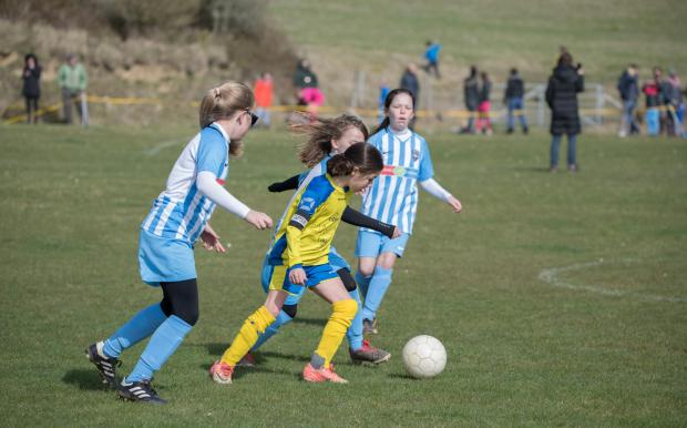 Isle of Wight County Press: Newport's Annie White (wearing yellow) fends off challenges from several Vectis players.