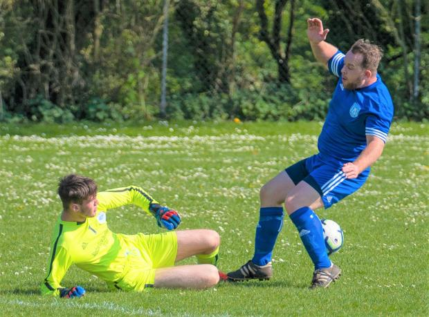 Isle of Wight County Press: Ryde Saints keeper Ben Orton slides in to stop Carisbrooke scoring.